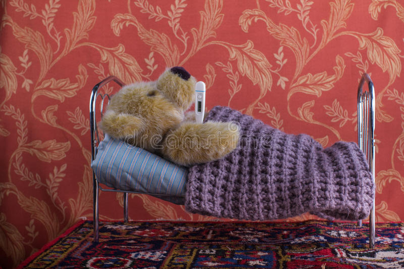 Zieke eenzame teddybeer die met thermometer in bed liggen stock afbeeldingen