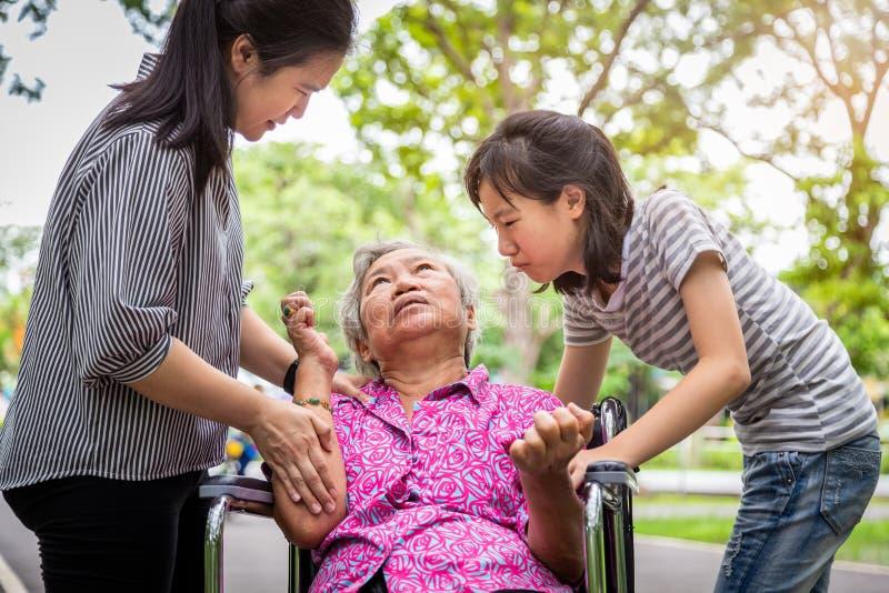 Zieke hogere grootmoeder in rolstoel met toevallen in openlucht, bejaarde geduldige uitbarstingen die aan ziekte lijden met stock foto