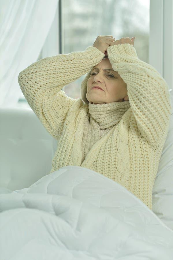 Zieke hogere vrouw in bed stock afbeeldingen