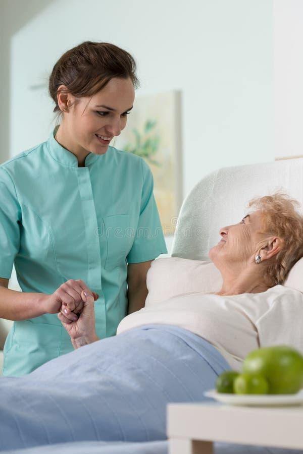 Zieke hogere vrouw in het ziekenhuis stock afbeeldingen