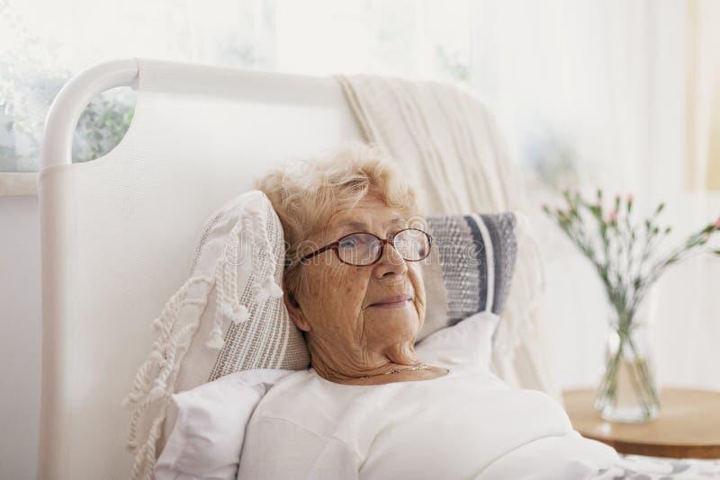 Zieke hogere vrouw met glazen die in het ziekenhuisbed liggen stock afbeelding