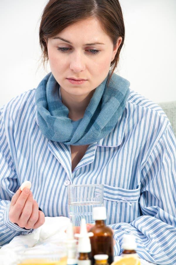 Zieke jonge vrouw die geneeskunde nemen stock fotografie