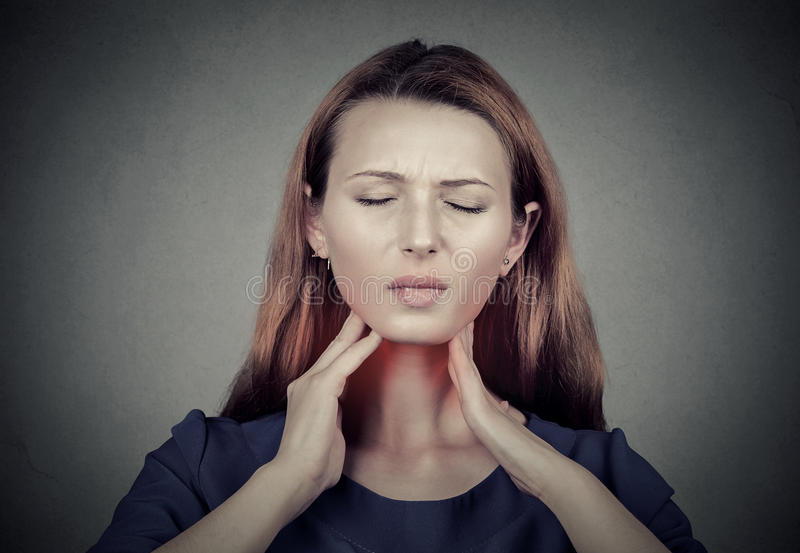 Zieke jonge vrouw die pijn in haar keel hebben stock fotografie