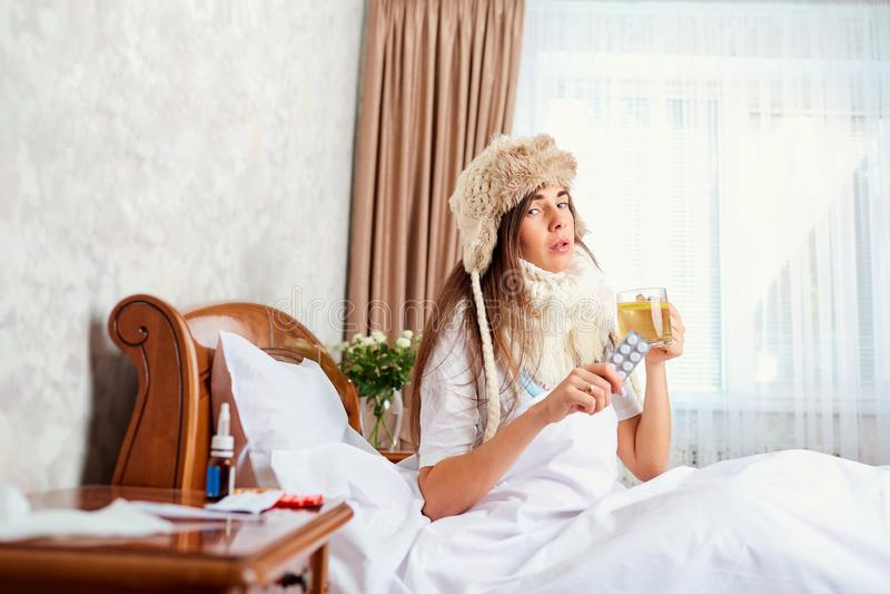 Zieke jonge vrouw op het bed in de ruimte royalty-vrije stock afbeelding