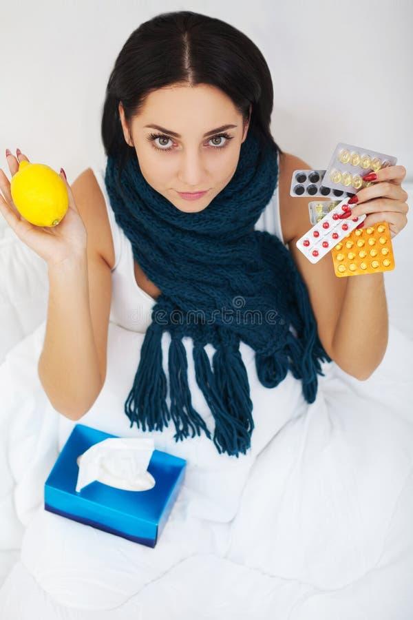 Zieke jonge vrouw thuis op de bank, behandelt zij met een bla stock afbeelding