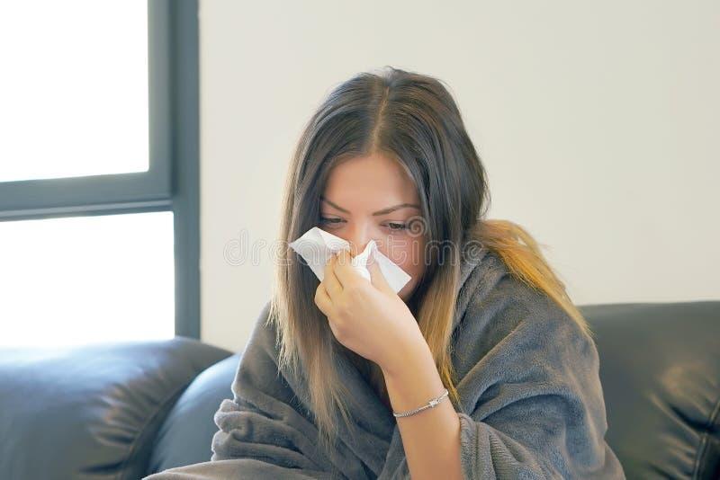 Zieke jonge vrouwenzitting op een zwarte laag, en het blazen van zijn neus in een servet stock foto