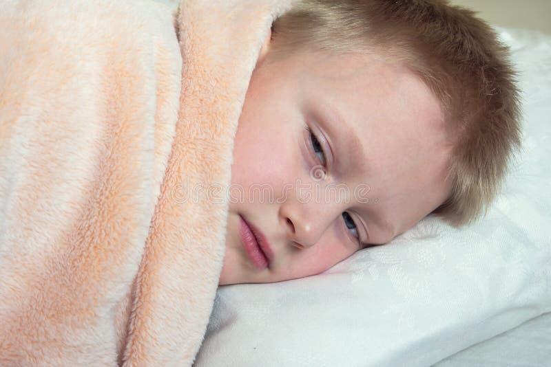 Zieke jongen die in bed ligt stock afbeelding