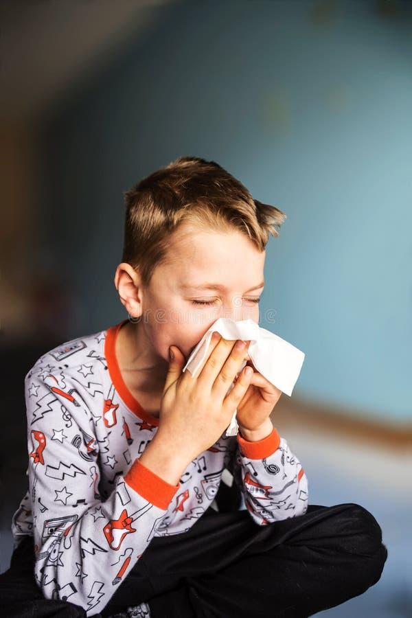 Zieke jongen die zijn neus blaast stock afbeeldingen