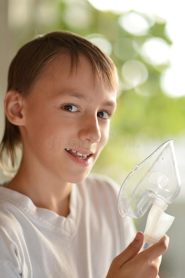 Zieke jongen met inhalator stock afbeelding