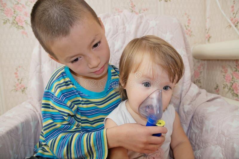 Zieke kinderen - de jongen maakt verstuiversmasker voor inhalatie voor weinig zuster, ademhalingsprocedure door longontsteking of royalty-vrije stock afbeelding