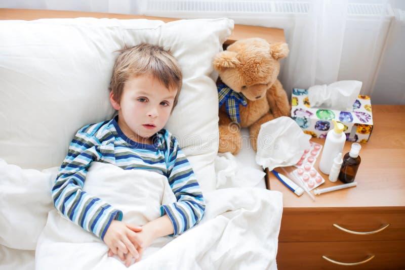 Zieke kindjongen die in bed met een koorts liggen, het rusten royalty-vrije stock fotografie