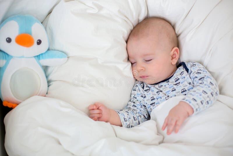Zieke kindjongen die in bed met een koorts liggen, die thuis rusten stock foto
