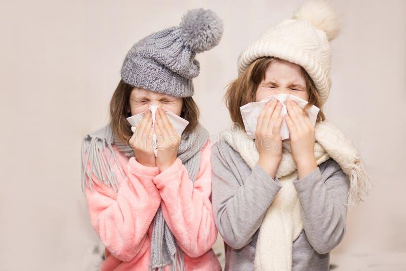 Zieke kleine zusters in hoeden blazende neuzen met servetten samen royalty-vrije stock foto