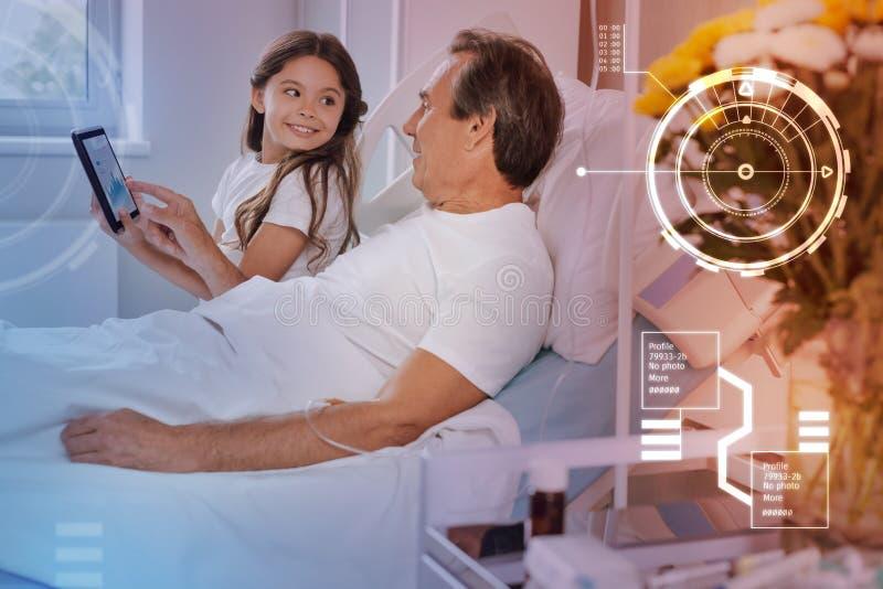 Zieke mens in bed blijven en zijn dochter die hem een modern apparaat tonen royalty-vrije stock afbeeldingen