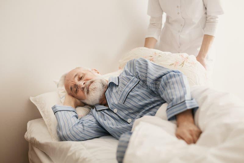 Zieke mens die blauwe pyjama dragen die in bed bij verpleeghuis liggen royalty-vrije stock afbeelding