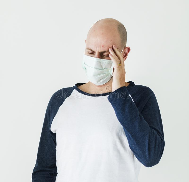Zieke mens die chirurgisch masker dragen die een hoofdpijn hebben stock afbeeldingen