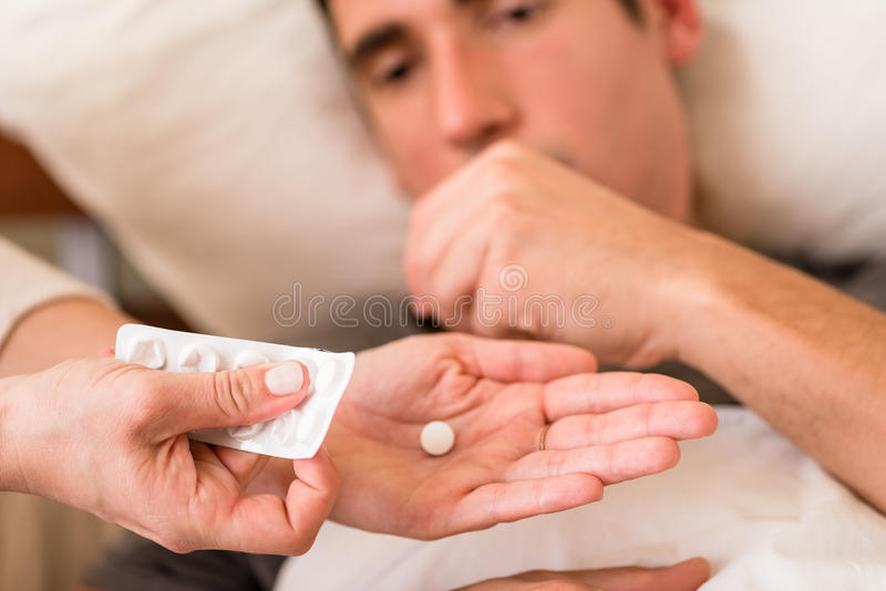 Zieke mens die die medicijn nemen door een verpleegster wordt aangeboden stock foto's