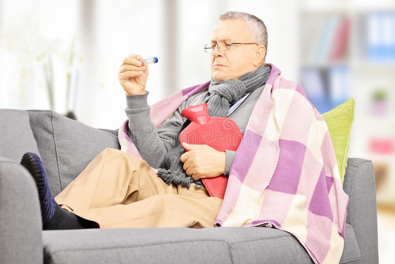 Zieke mens op een bank met een warm waterfles die thermomete bekijken stock fotografie
