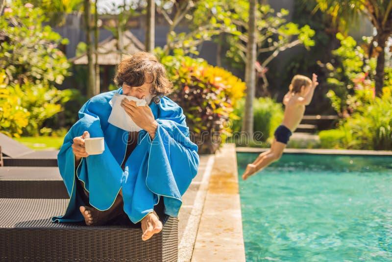Zieke mensenreiziger De man ving een koude op vakantie, zit droevig bij de pool het drinken thee en blaast zijn neus in een serve stock foto's