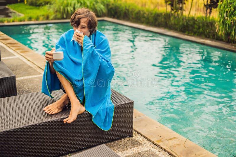 Zieke mensenreiziger De man ving een koude op vakantie, zit droevig bij de pool het drinken thee en blaast zijn neus in een serve stock afbeelding