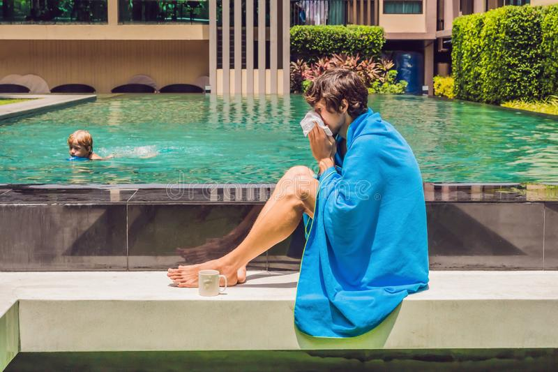 Zieke mensenreiziger De man ving een koude op vakantie, zit droevig bij de pool het drinken thee en blaast zijn neus in een serve stock afbeeldingen