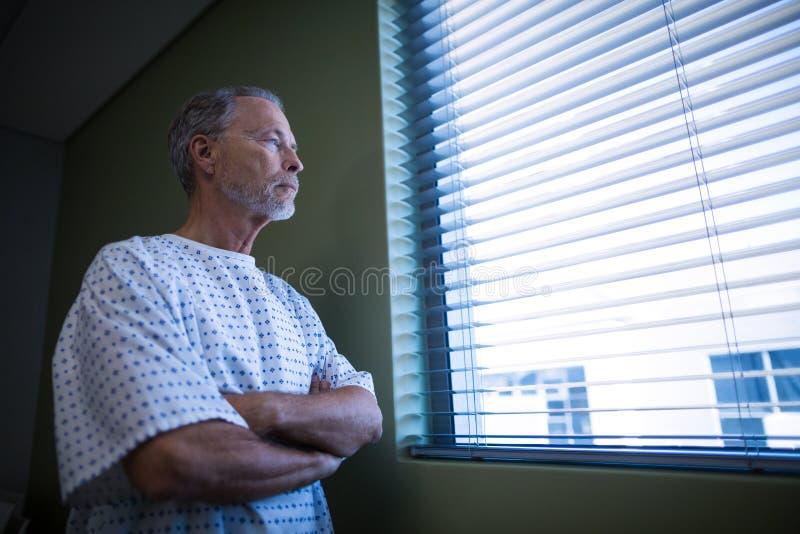 Zieke patiënt die door vensterzonneblinden kijken stock foto