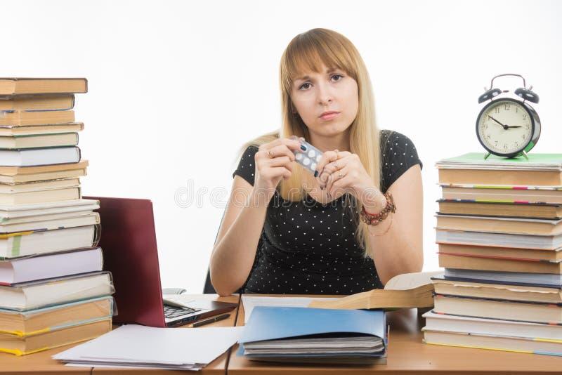 Zieke studentenzitting bij de lijst met tabletten in handen royalty-vrije stock afbeelding