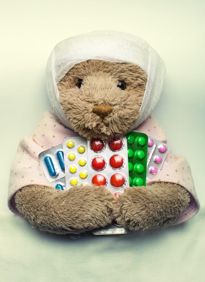 Zieke teddybeer in bed stock afbeelding