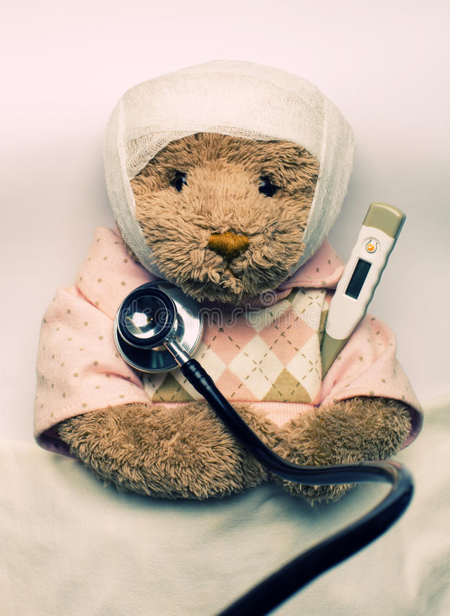 Zieke teddybeer in bed stock fotografie