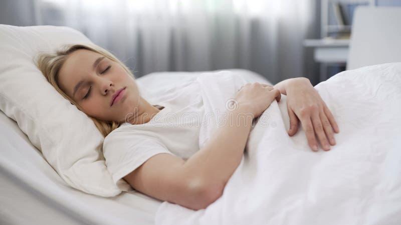Zieke tienerslaap in bed thuis, bleek gezicht met zwarte cirkels onder ogen royalty-vrije stock afbeeldingen