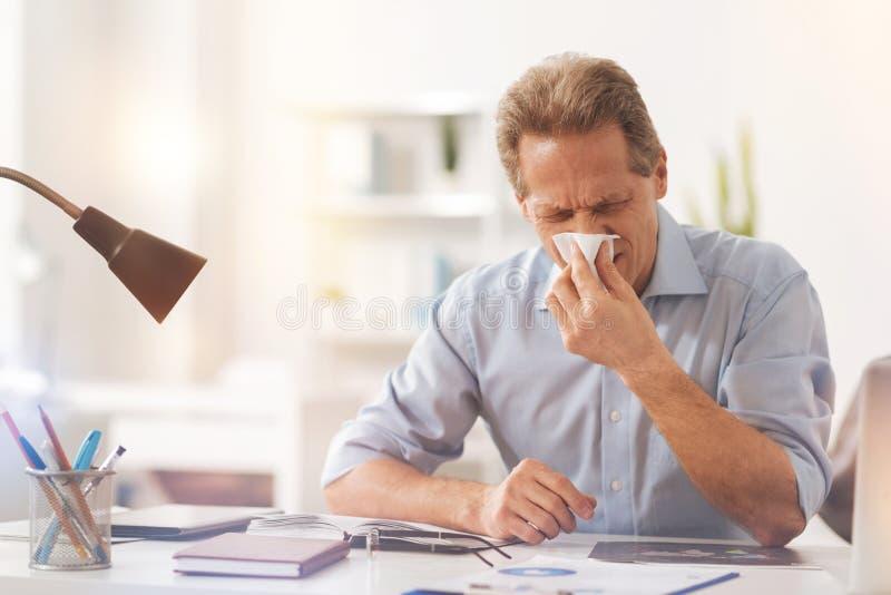 Zieke volwassen mens die zijn neus blazen stock afbeelding
