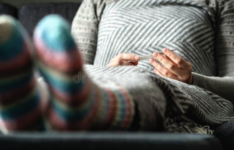 Zieke vrouw die met griep en koude koorts en lichaamstemperatuur met thermometer controleren Zieke persoonszitting op laag thuis stock foto's