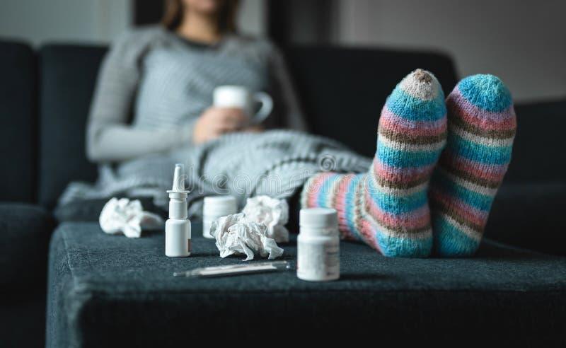 Zieke vrouw die op laag rusten die hete kop thee houden Zieke persoon met griep, koude, koorts of viruszitting op bank thuis in d stock foto
