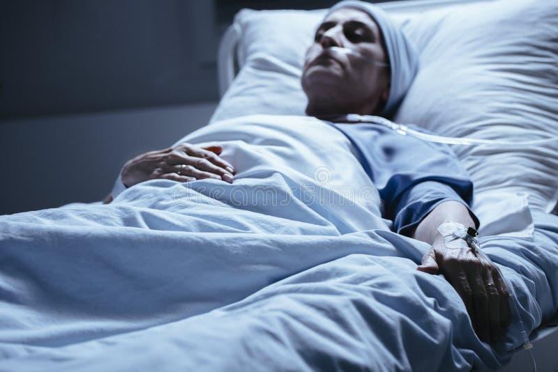 Zieke vrouw met catheter die in het ziekenhuisbed tijdens chemothera liggen stock afbeelding
