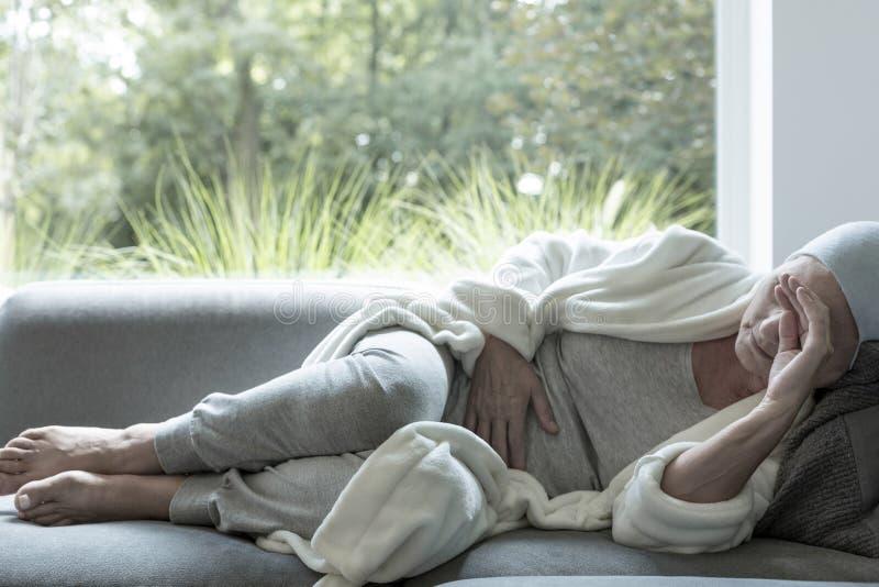 Zieke vrouw met een hoofdpijn die op een bank liggen stock afbeelding