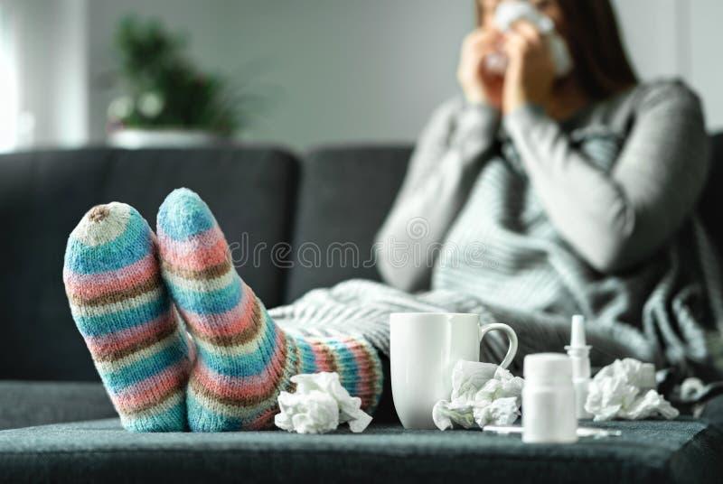 Zieke vrouw met griep, koude, koorts en hoestzitting op laag thuis Zieke persoons blazende neus en het niezen met weefsel royalty-vrije stock afbeeldingen