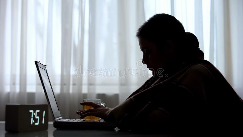 Zieke vrouwelijke freelancer werkt vroeg in de ochtend aan laptop en drinkt thee stock foto