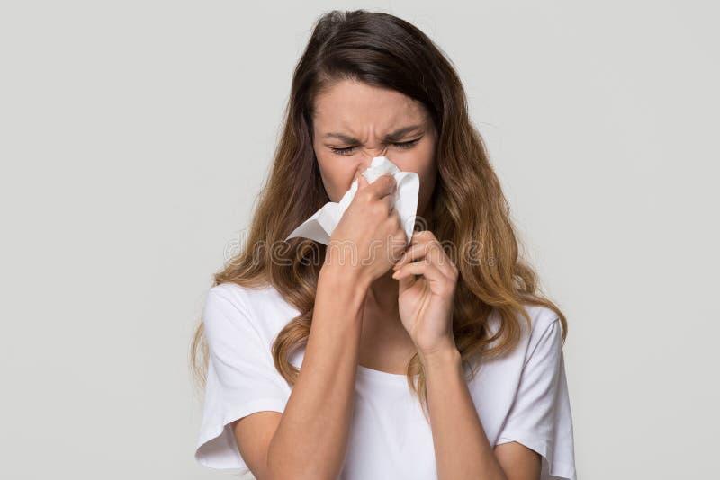 Zieke vrouwen blazende lopende neus in weefsel dat op achtergrond wordt geïsoleerd stock foto's