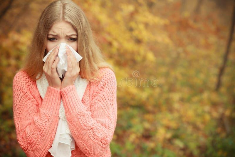 Zieke zieke vrouw die in de herfstpark in weefsel niezen stock afbeeldingen
