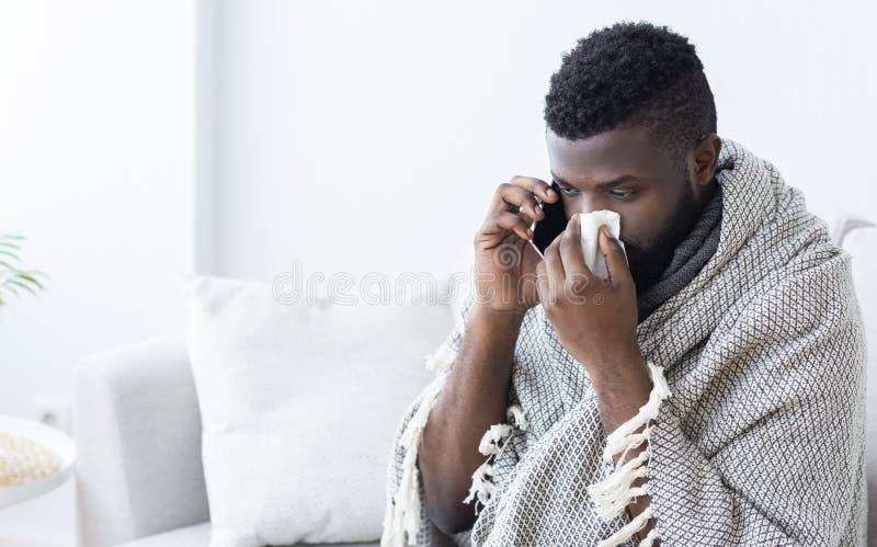 Zieke zwarte kerel die een ziekenwagen, gevangen griep roepen royalty-vrije stock afbeeldingen