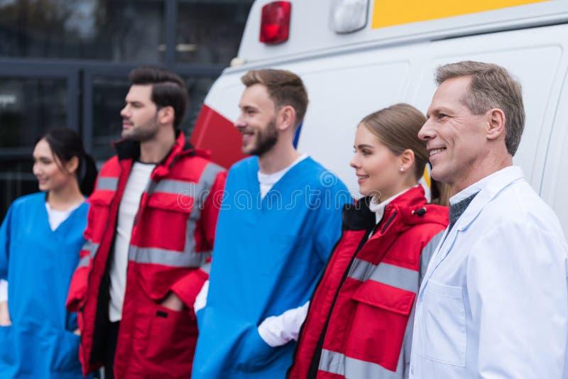 ziekenwagen artsen die team werken dat en zich vooraan glimlacht bevindt stock foto's
