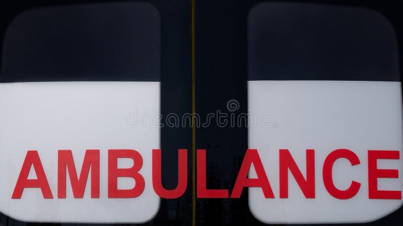 ziekenwagen Rode inschrijving op het autoraam noodsituatie Close-up Concept voor ontwerp op het thema van gezondheid en het helpe stock afbeelding