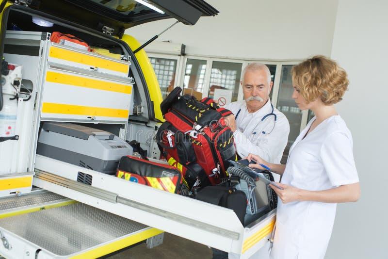 Ziekenwagen verpleegster en artsenverpakkingstoestel in voertuig royalty-vrije stock afbeeldingen