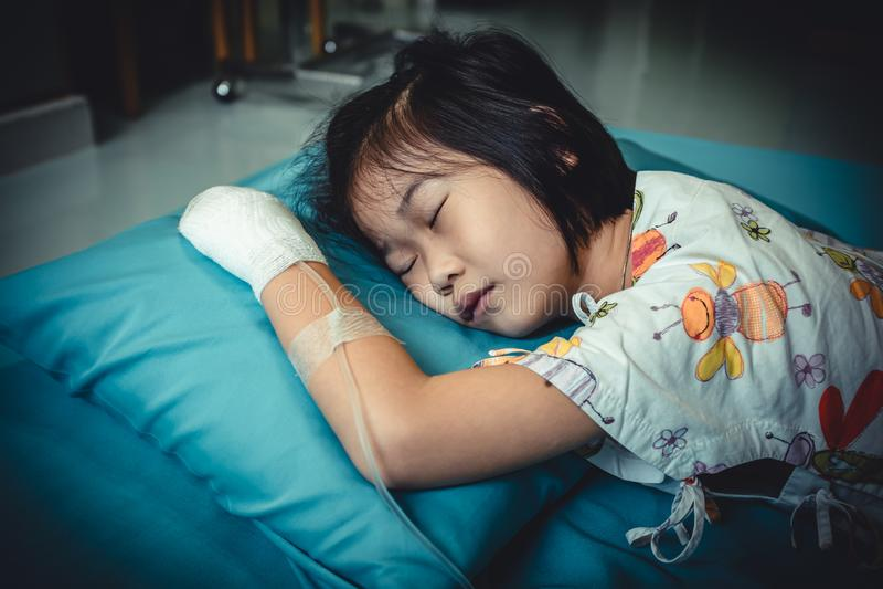 Ziekte Aziatisch kind dat in het ziekenhuis met zoute intraveneus op hand wordt toegelaten stock afbeeldingen