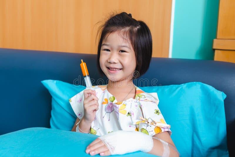 Ziekte Aziatisch kind dat in het ziekenhuis met zoute intraveneus op hand wordt toegelaten stock fotografie