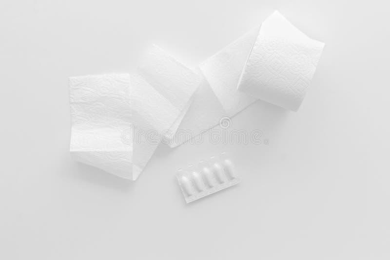 Ziekte van dubbelpuntconcept met toiletpapierbroodje en rectale zetpil op witte hoogste mening als achtergrond stock afbeelding