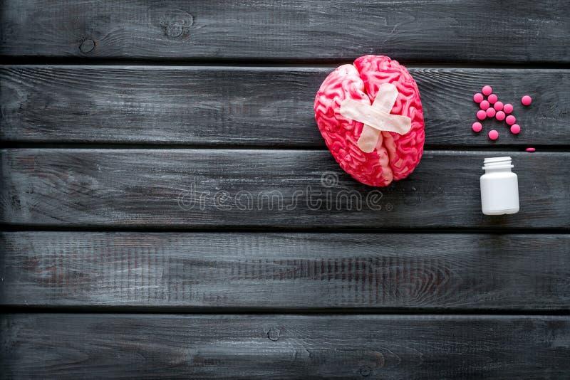 Ziekte van het hersenenconcept met hersenen met kruisvormig flard en pillen op houten hoogste mening als achtergrond stock afbeelding