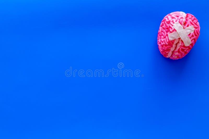 Ziekte van het hersenenconcept met hersenen met kruisvormig flard op blauwe hoogste mening als achtergrond stock foto