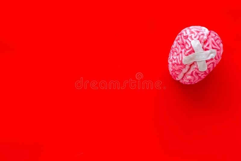 Ziekte van het hersenenconcept met hersenen met kruisvormig flard op rode hoogste mening als achtergrond royalty-vrije stock fotografie