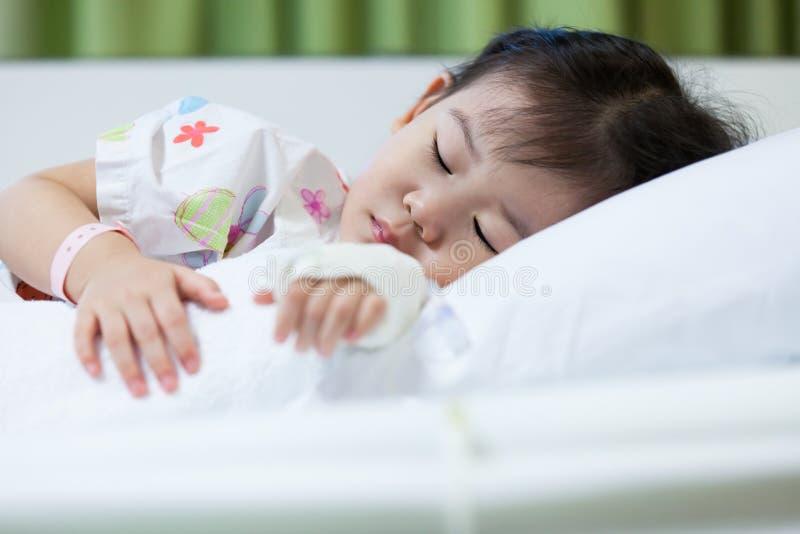 Ziektekind in het ziekenhuis, zout intraveneus (iv) op hand Aziaat stock foto